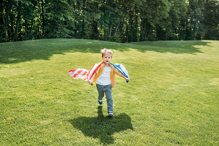 adorable little boy with american flag running on grass in park