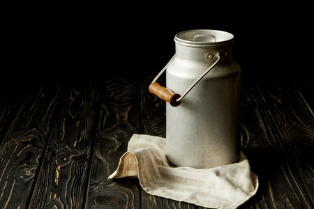 milk in aluminium can on sackcloth on black background