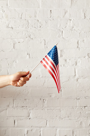 cropped image of man holding american flagpole against white brick wall Stockfoto