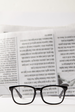 selective focus of black eyewear and newspaper on background, black and white Stockfoto