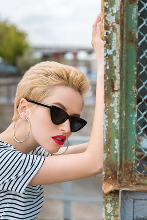 stylish girl in sunglasses and with short hair leaning on fence