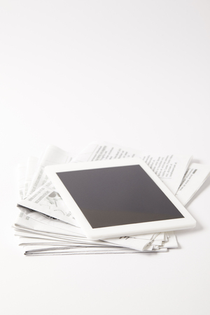 digital tablet with blank screen on pile of newspapers, on white Stockfoto