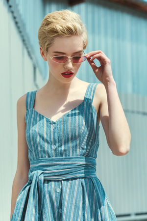stylish girl with short hair posing in trendy blue dress and pink sunglasses