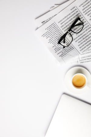 flat lay with eyeglasses, coffee, laptop and newspapers, on white with copy space Stock Photo