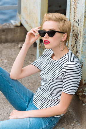 stylish girl in sunglasses and with short hair sitting and leaning on wall