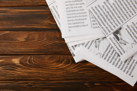 top view of pile of newspapers on wooden background with copy space Stockfoto