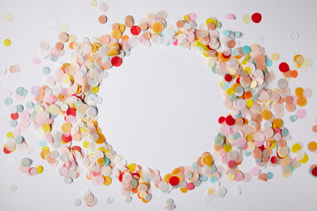 top view of circle of colored confetti pieces on white surface