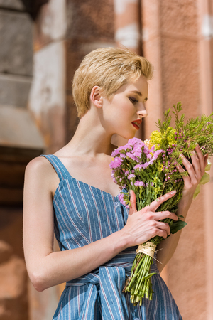 beautiful girl in trendy blue dress with bouquet of flowers Stock Photo