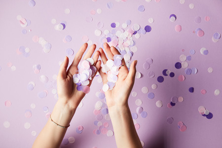 cropped image of woman holding falling confetti pieces on surface Stock Photo