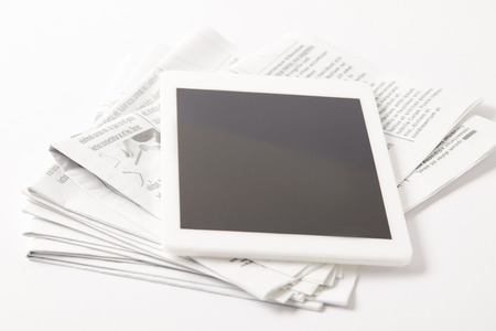 close up of pile of newspapers with digital tablet, on white