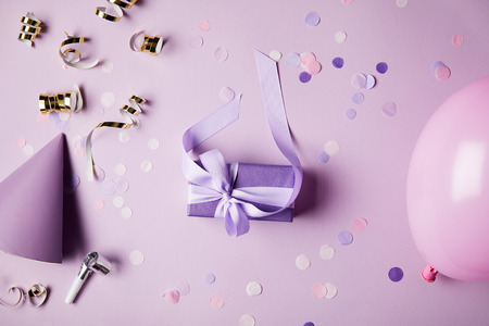 top view of one violet present box, balloon, party hat and confetti pieces on surface