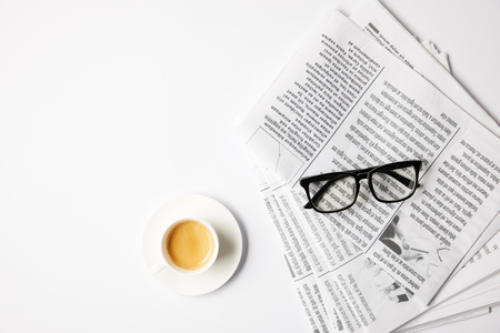 top view of cup of coffee and eyeglasses on newspapers, on white table Archivio Fotografico - 106072841