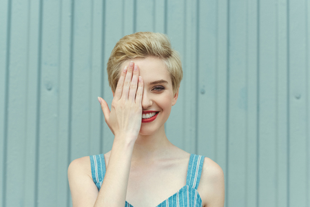 cheerful girl with short hair closing one eye