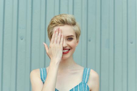 cheerful girl with short hair closing one eye Foto de archivo