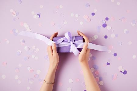 bijgesneden afbeelding van vrouw met huidige doos aan tafel met confetti stukken