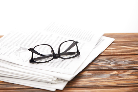 eyeglasses on pile of newspapers on wooden table, on white Stockfoto