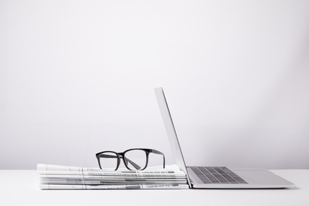 laptop and eyeglasses on heap of newspapers, on white Foto de archivo