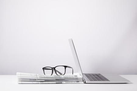 laptop e occhiali sul mucchio di giornali, su bianco