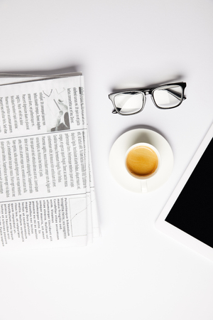 flat lay with eyeglasses, coffee, digital tablet and newspapers, on white Stockfoto