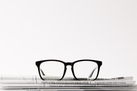 close up of eyewear on pile of newspapers, isolated on white background with copy space