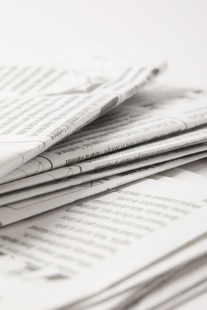 close up of heap of daily newspapers with information, on white