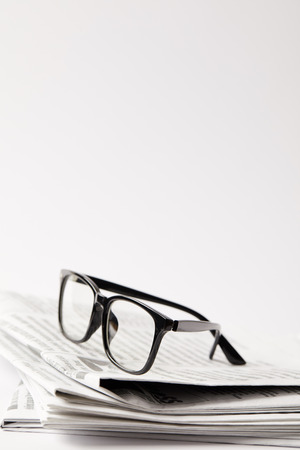 close up of newspapers with black eyeglasses, on white with copy space 版權商用圖片 - 106072966