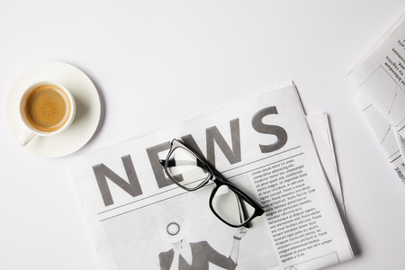 flat lay with eyeglasses, cup of coffee and newspapers, on white table