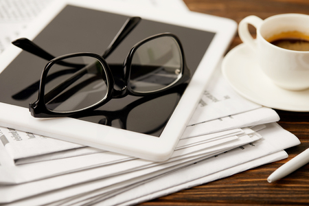 eyeglasses, coffee cup, digital tablet and newspapers on wooden table