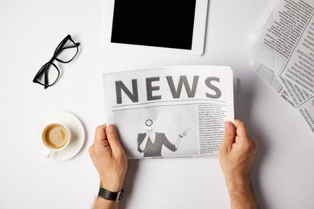 beschnittene Ansicht des Geschäftsmannes, der Zeitung am weißen Tisch mit digitaler Tablette, Kaffee und Brille liest Standard-Bild