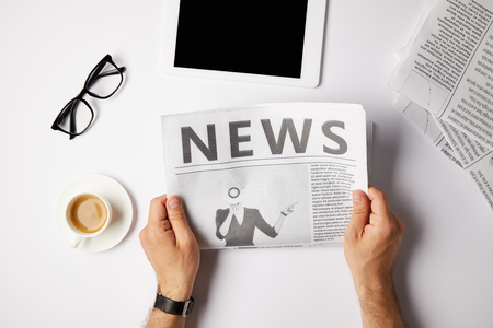 Vista recortada del empresario leyendo el periódico en la mesa blanca con tableta digital, café y anteojos Foto de archivo