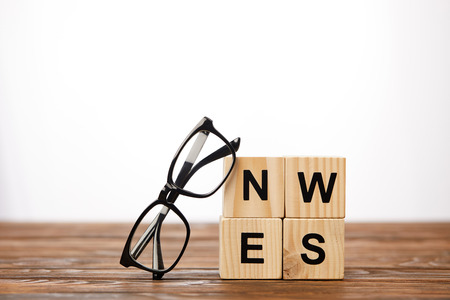 eyeglasses and alphabet cubes making word news on wooden surface, on white background 写真素材