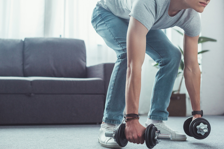 cropped view of teen boy squatting with dumbbells at home