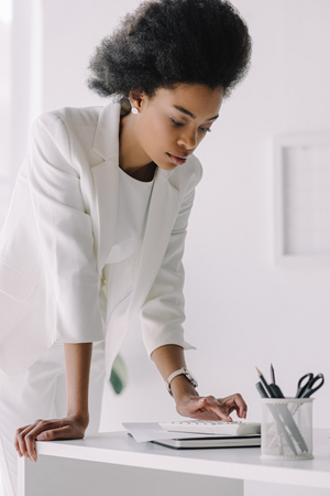 attractive african american businesswoman using calculator in office Reklamní fotografie