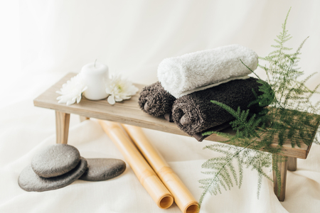 close up view of arrangement of spa treatment accessories with towels and pebbles on white background Stockfoto