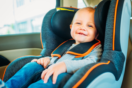 happy little baby sitting in child safety seat in car and looking at camera Stock Photo