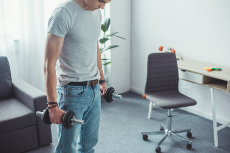 young boy training with dumbbells at home Stockfoto