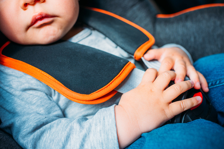 cropped shot of little baby sitting in child safety seat in car Stock Photo