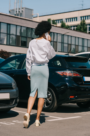 back view of african american businesswoman talking by smartphone on parking Stock Photo