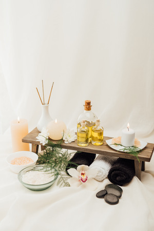 close up view of arrangement of spa treatment accessories with towels, oil and salt on white background