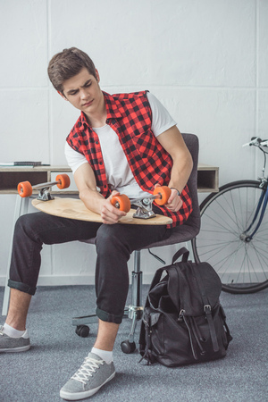 young skateboarder fixing his longboard at home