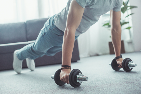 partial view of young man doing push ups with dumbbells at home
