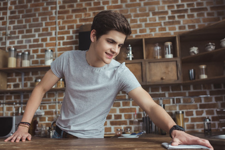 handsome teen boy cleaning table with rag in kitchen Imagens