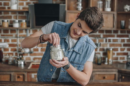 smiling teenager taking dollar banknotes from saving glass jar for money Stok Fotoğraf