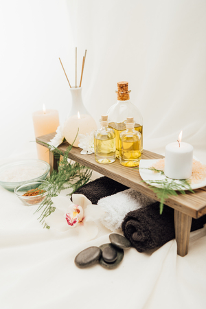 close up view of arrangement of spa treatment accessories with essential oil, salt and candle on white background