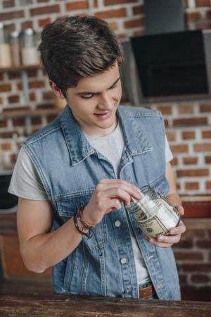 teen boy putting dollar banknotes into moneybox
