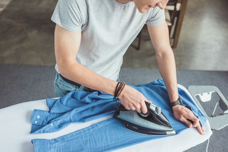 cropped view of teenager ironing blue shirt with iron at home