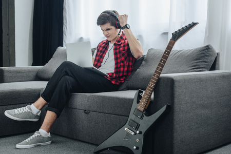 teen boy with headphones playing game on laptop while sitting on sofa with electric guitar near