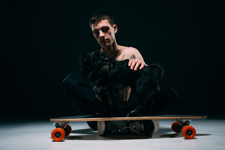 Man with tattoos stroking black dog on longboard on dark background