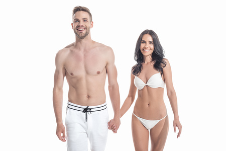 beautiful cheerful couple in swimwear holding hands, isolated on white