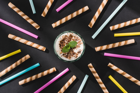 top view of milkshake with chocolate shavings and mint surrounded by sweet and drinking straws